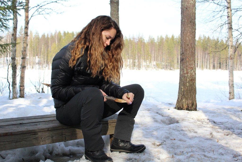 Katie whittling something very pointy out of wood, perhaps a chop stick?